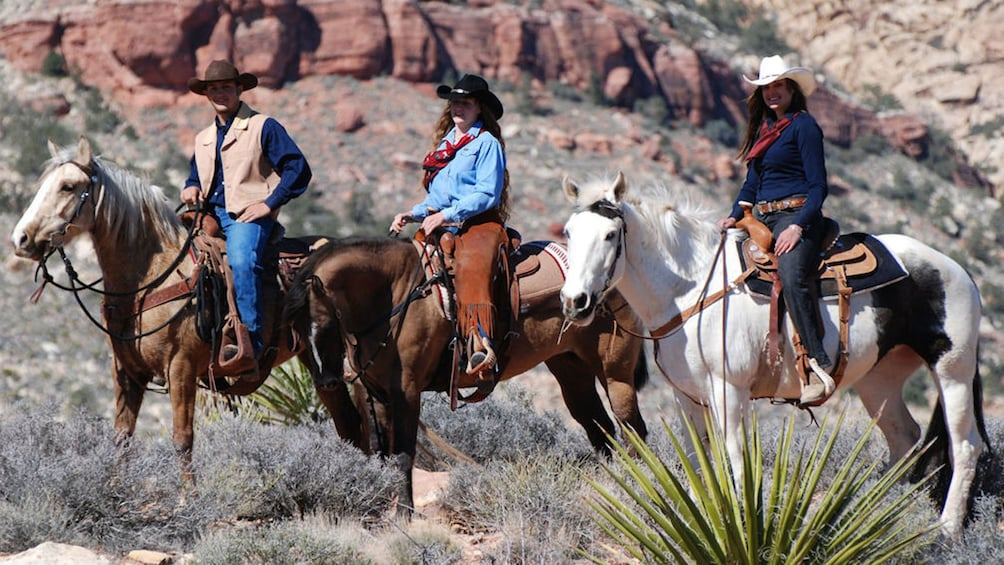 Show item 3 of 5. Three horseback riders on the Wild West Horseback Riding tour in Las Vegas