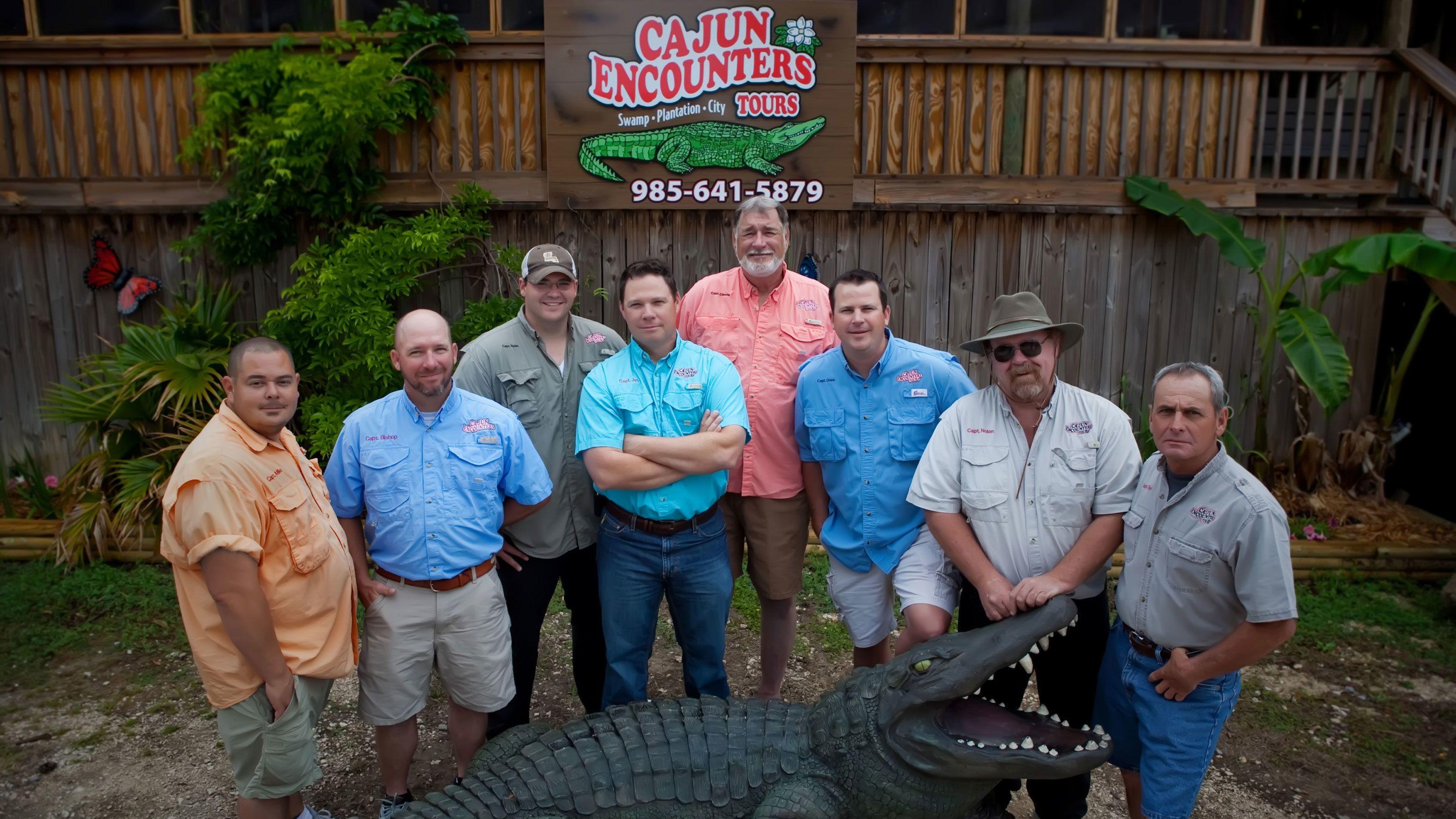 eight men gather round alligator replica at alligator farm in New Orleans