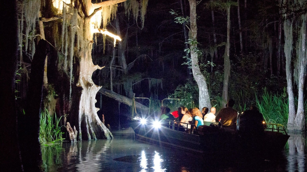 Show item 1 of 8. boat and passengers on swamp lake at night in New Orleans