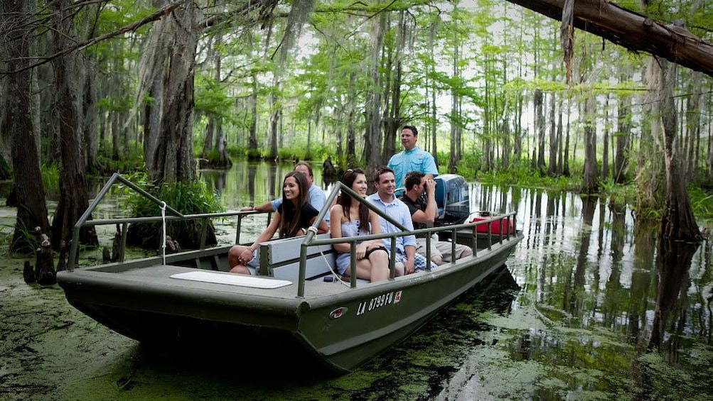 Show item 4 of 8. boat and passengers sail into swamp lands in New Orleans