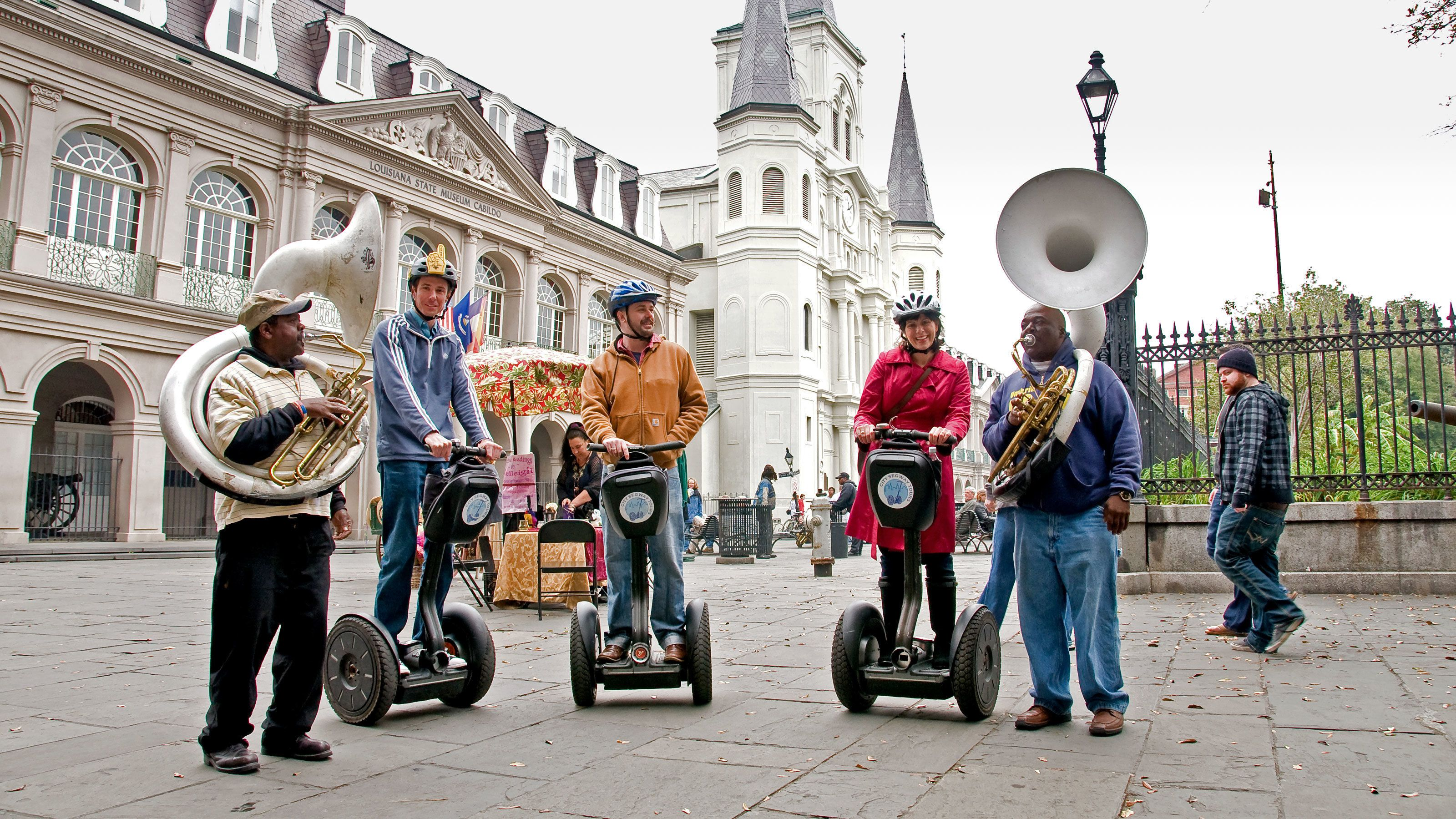 three people on segways and two men with tubas in New Orleans