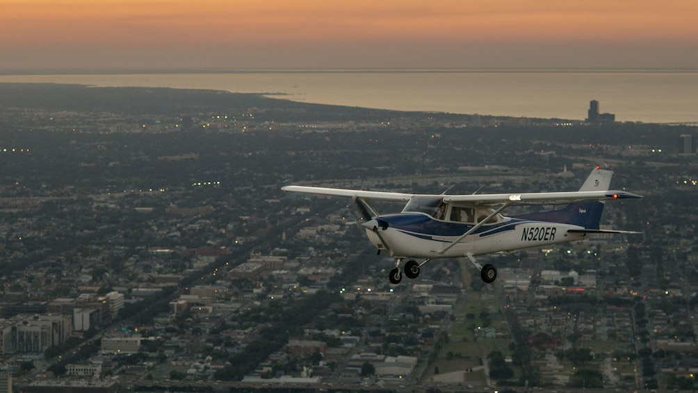 Show item 3 of 5. airplane flying above city of New Orleans