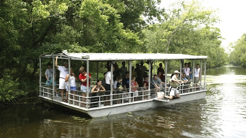passengers aboard swamp boat on river in New Orleans