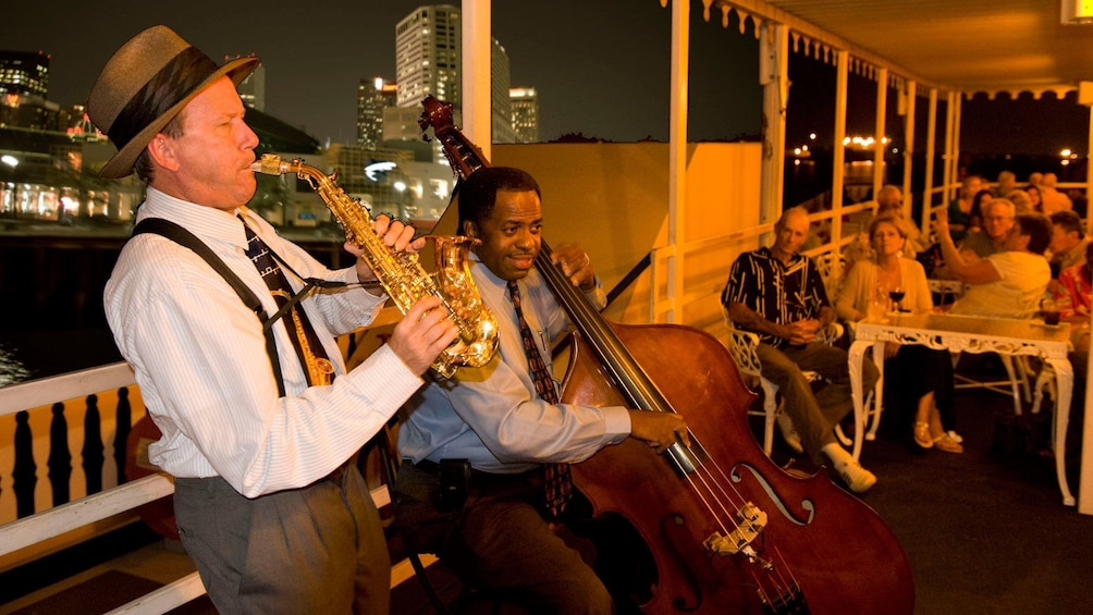 Show item 3 of 9. jazz musicians playing for crowd on river boat in New Orleans