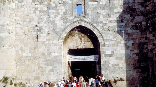 People at the entrance to a stone gate in Jerusalem