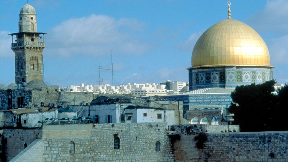 Show item 3 of 6. The dome of the rock with a minaret off in the distance in Jerusalem