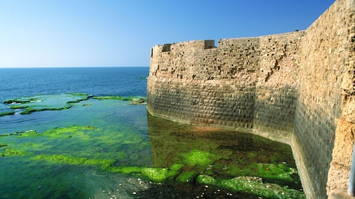 Walls of an ancient city on the water in Israel