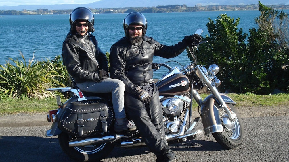 Harley rider and passenger parked along the coast in Auckland