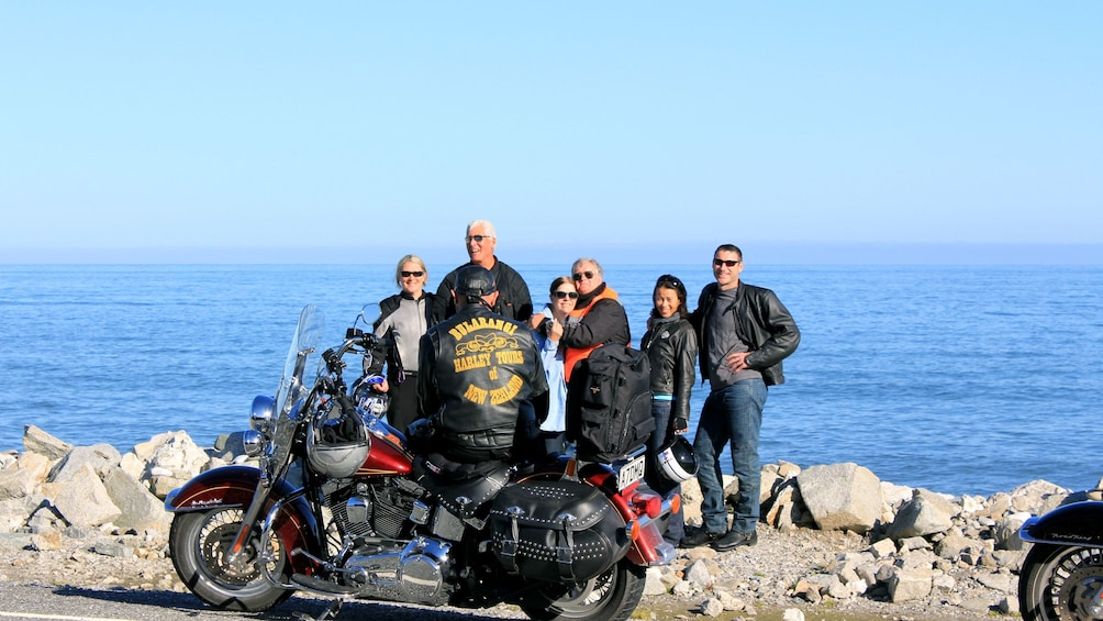 Harley riding group posing for a picture along the coast in Auckland