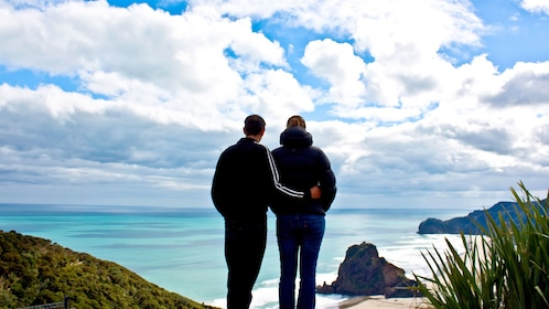 Couple looking out at the ocean from Waitakere Ranges Regional Parklands in Auckland