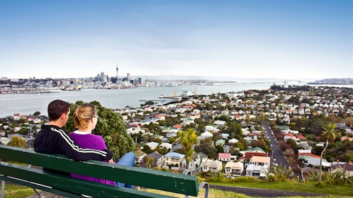 Couple on a bench at Waitakere Ranges park overlooking the city in Auckland