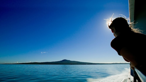 Silhouette of a woman hanging over the railing of a boat on the way to Rangitoto Island