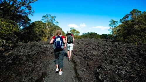 Hiking pair of women on a volcanic rock path on Rangitoto Island