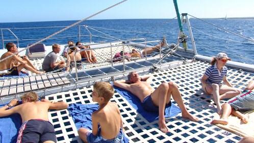 catamaran passengers sunbathing on the canopy in Mauritius