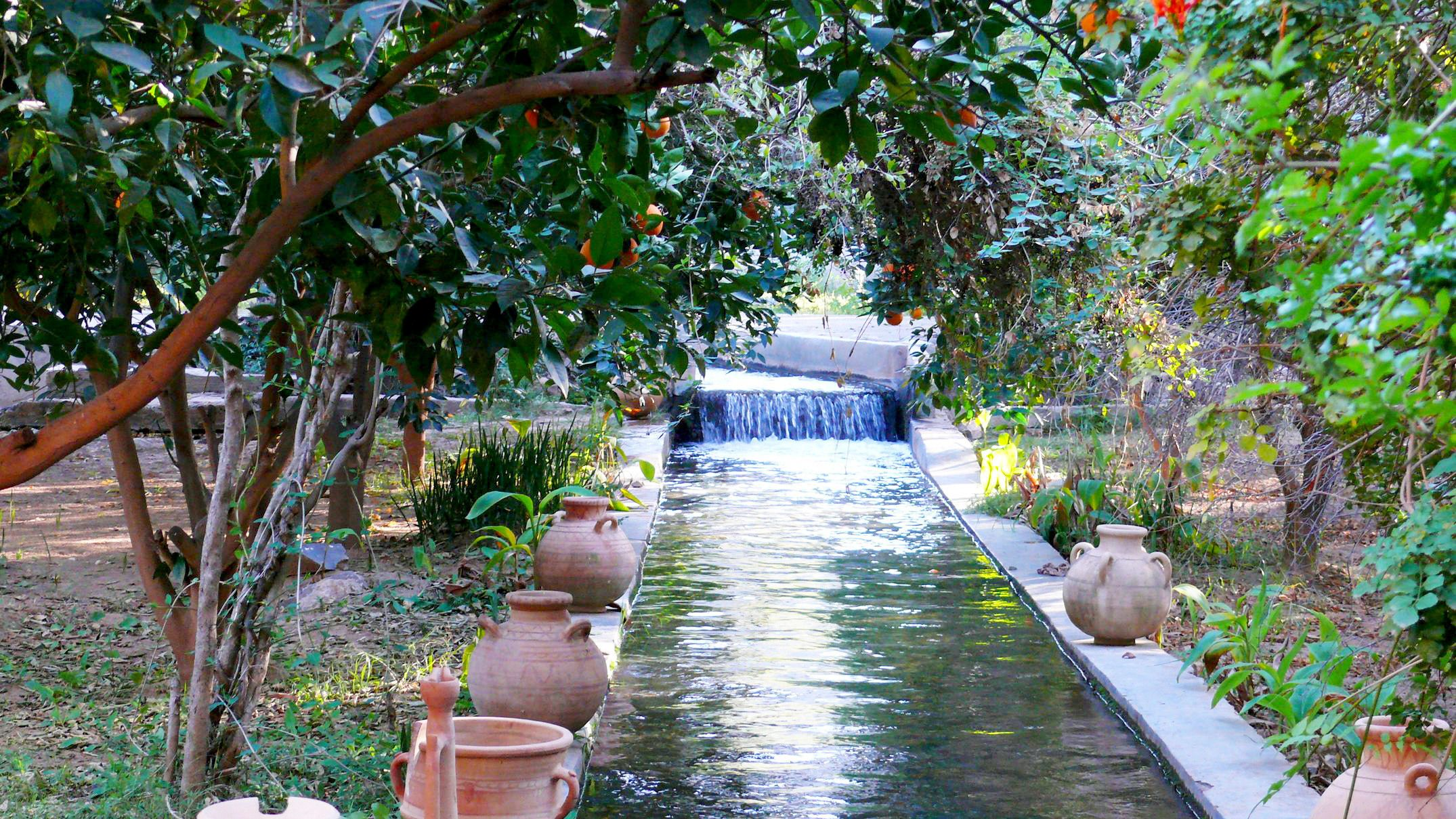 Clay pots sit along a stream running through a garden in Taroudant