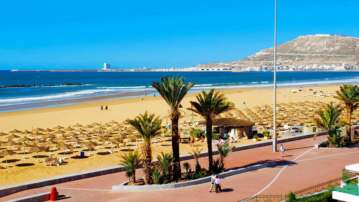 People walking on the promenade along the sandy coast of Agadir