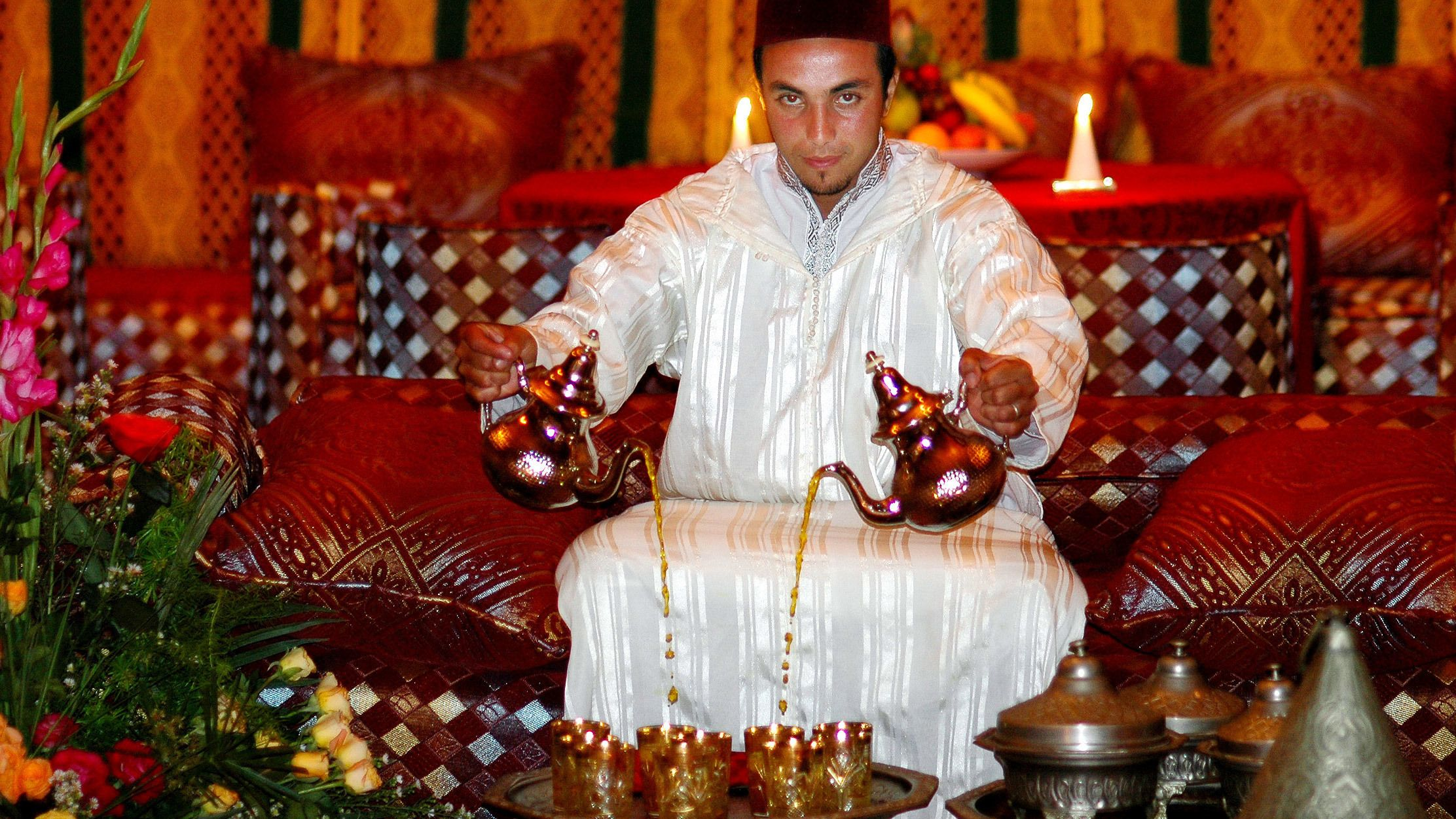 Server pouring two tea pots simultaneously in Agadir
