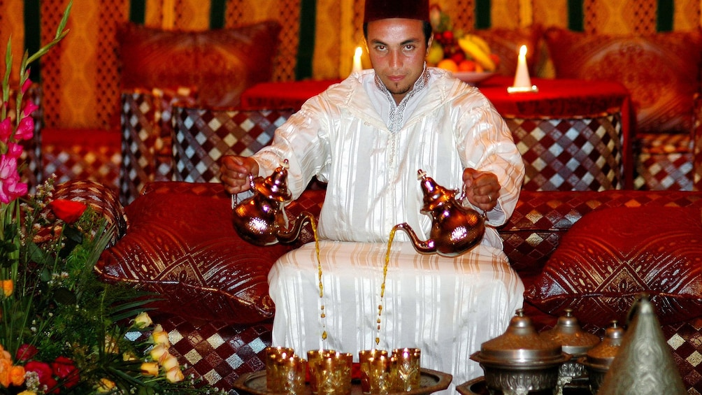 Show item 2 of 5. Server pouring two tea pots simultaneously in Agadir
