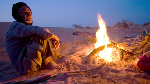 Berber man sitting by a campfire in the desert in