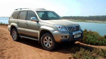Show item 5 of 5. SUV on a dirt road along a river near Assaka