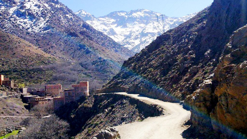 Stone houses of a berber village at the bottom of the snow-covered Atlas Mountains