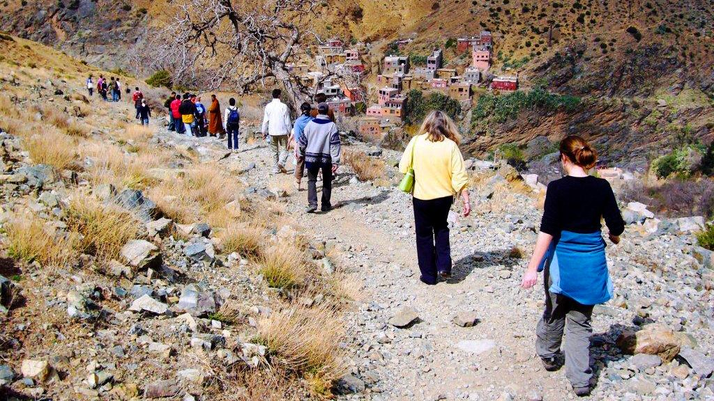 Hiking group on a path with a berber village in the distance