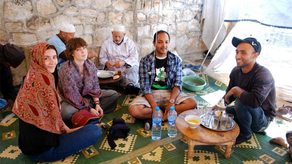 Tour group sitting on a rug and enjoying refreshments in Agadir