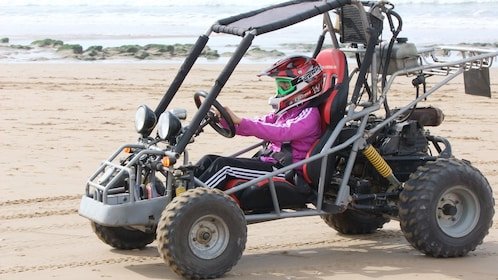 Young girl driving a dune buggy on the beach in Agadir
