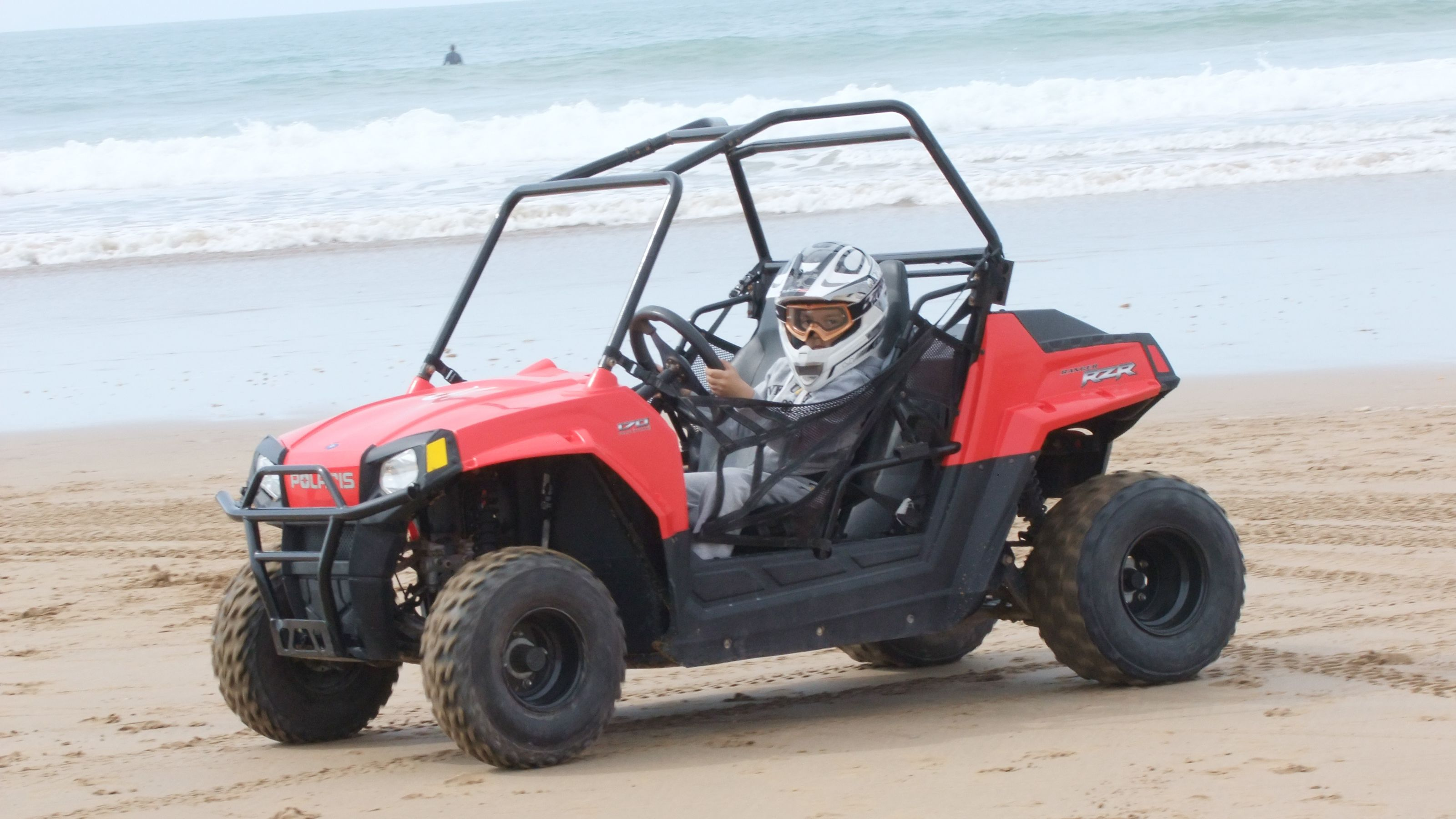 Kid driving a dune buggy on the beach near the water in Agadir