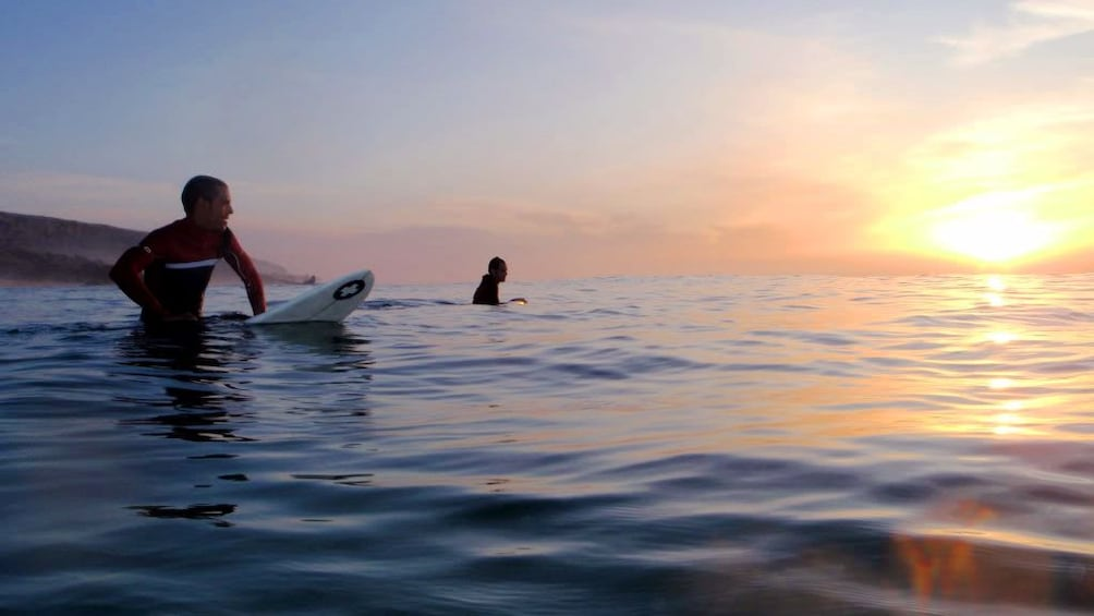 Show item 4 of 5. Pair of surfers sitting on their surfboards in the water at sunset in Agadir