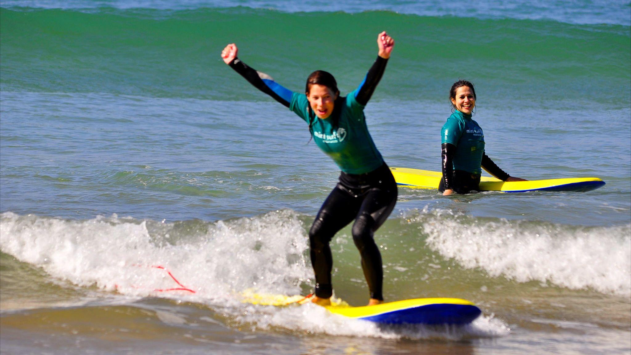 Triumphant woman catching a wave in Agadir