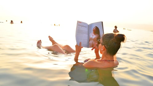 Woman floats in the Dead sea while reading a magazine