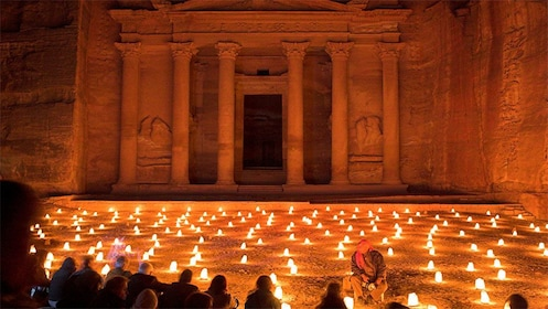 Lit lanterns on the ground leading to Al Khazneh temple in Petra