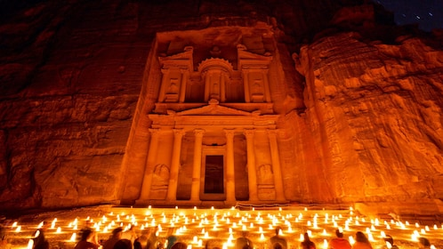 Al Khazneh temple illuminated at night by lanterns on the ground at Petra