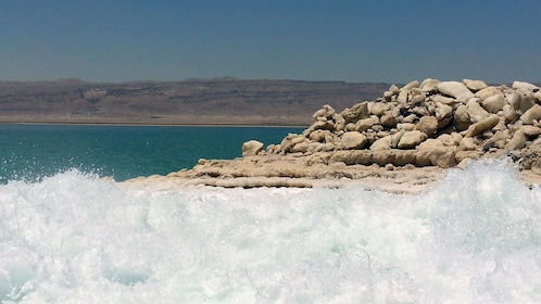 Waves crashing on the rocky shore of the Dead Sea