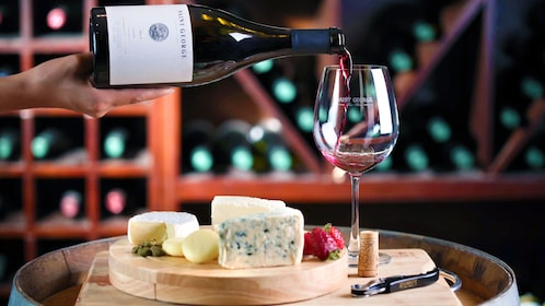 Person pouring wine into a glass accompanied with gourmet cheese and fruit
