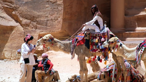 Woman talking to a camel with rider outside Petra