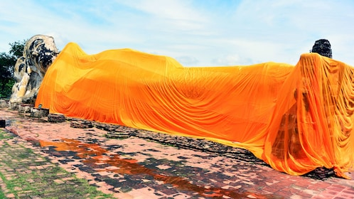 A lying buddha covered in a bright orange cloth in bangkok