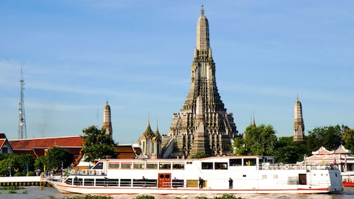 a river boat sailing past a temple in bangkok