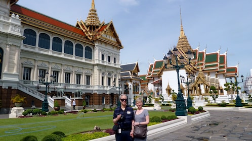 Two people outside the grand palace in bangkok