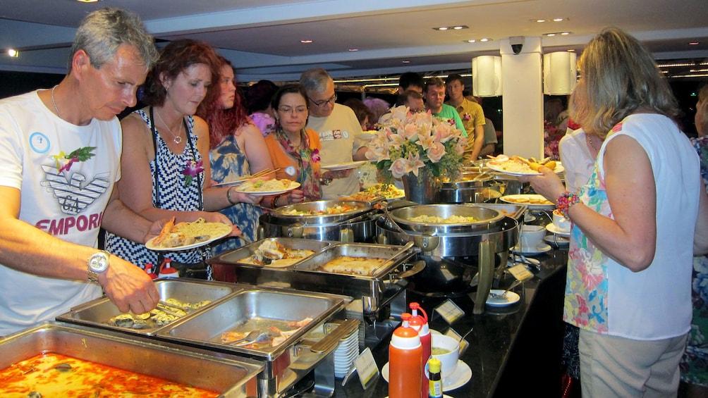 正在顯示第 4 張相片,共 9 張。 people getting food from a buffet on a dinner cruise in bangkok