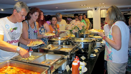 people getting food from a buffet on a dinner cruise in bangkok
