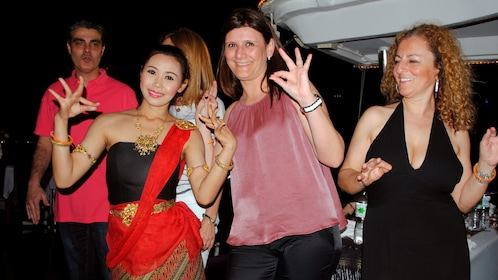People with a performer on a dinner cruise in bangkok