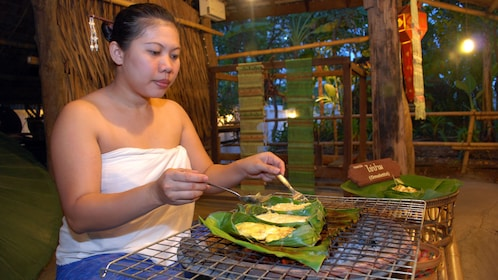 A woman preparing a traditional meal in Bangkok