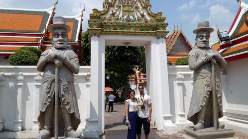 Two people standing at the entrance to a temple in bangkok