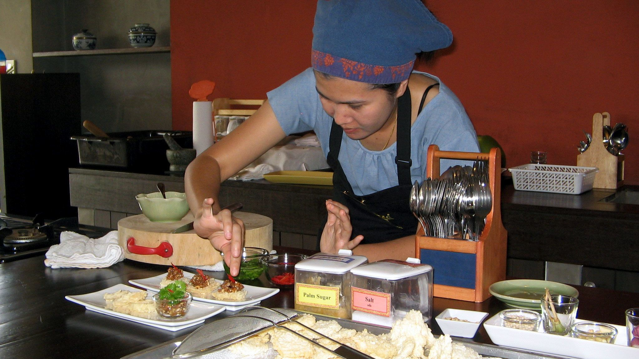 A cooking instructor plating food at a class in Bangkok