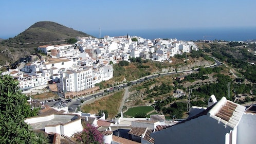 city of white buildings next to a coastal hill in Frigiliana