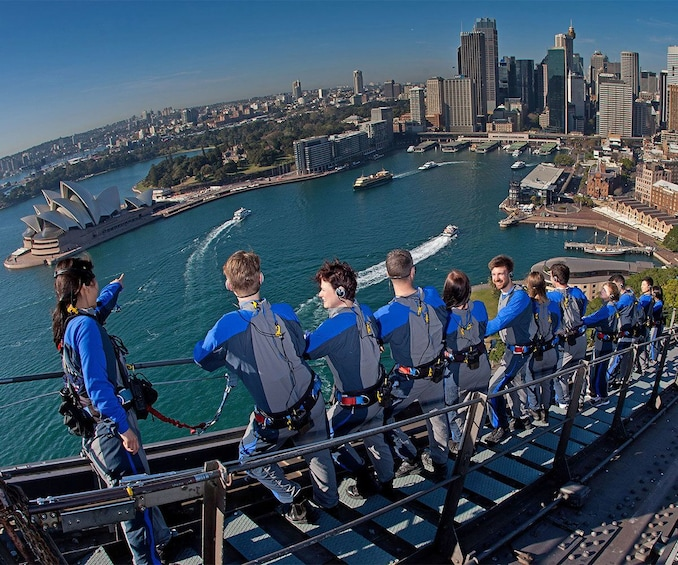 Show item 3 of 8. Close view looking down at the climbers from the Syndey Harbour Bridge with the cityscape visible in the distance