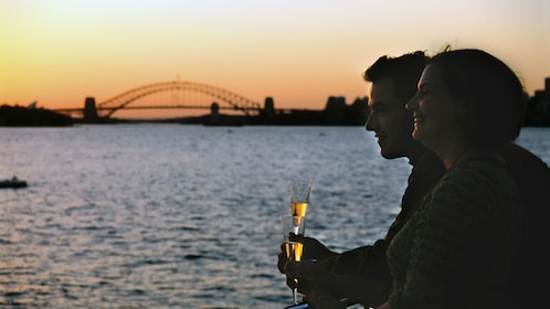 Couple looking out from the deck of a cruise ship on the Sydney Harbour with wine glasses in hand