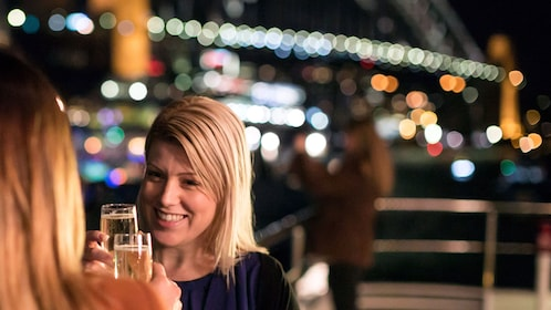 Sharp view of two guests enjoying wine aboard the cruise ship on the Sydney Harbour